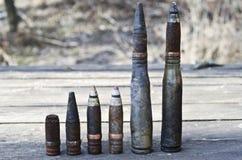 Gebrande die groot-kalibershells en kogels met en zonder kokers, door de explosie dichtbij op een houten lijst worden beïnvloed Stock Afbeelding