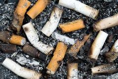 Gebrande sigaretuiteinden en as Stock Foto