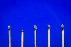 Gebrannte Matcheinstellung auf blauem Hintergrund für Ideen und inspiratio Stockbild