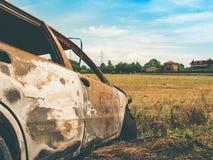 Gebranntes Auto auf einem wilden Gebiet Stockbilder