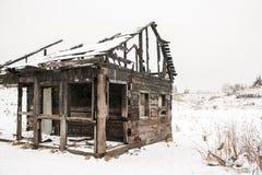 Gebranntes Holzhaus auf einem weißen Schnee Stockfotos