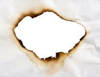 Gebranntes Loch im Papier Stockfotografie