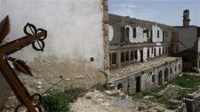Gebranntes und verrostetes Metallkreuz in den Ruinen des alten orthodoxen Klosters stock footage