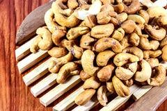 Gebratene Acajounüsse auf einem hölzernen Löffel Roasted salzte Acajounüsse auf weißem Hintergrund Gesundes Lebensmittel, Acajoub Stockbilder