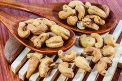 Gebratene Acajounüsse auf einem hölzernen Löffel Roasted salzte Acajounüsse auf weißem Hintergrund Gesundes Lebensmittel, Acajoub Lizenzfreie Stockbilder