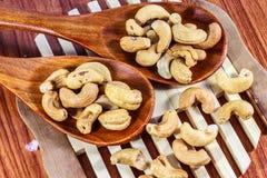 Gebratene Acajounüsse auf einem hölzernen Löffel Roasted salzte Acajounüsse auf weißem Hintergrund Gesundes Lebensmittel, Acajoub Stockfoto