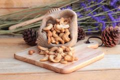Gebratene Acajounüsse mit natürlichem auf hölzernem Hintergrund Stockbild