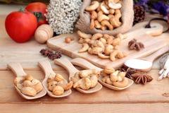 Gebratene Acajounüsse mit natürlichem auf hölzernem Hintergrund Stockfoto