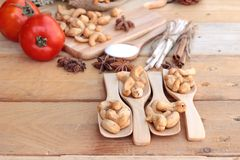 Gebratene Acajounüsse mit natürlichem auf hölzernem Hintergrund Lizenzfreie Stockfotos