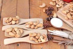 Gebratene Acajounüsse mit natürlichem auf hölzernem Hintergrund Stockfotos