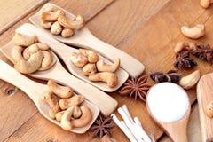 Gebratene Acajounüsse mit natürlichem auf hölzernem Hintergrund Stockbilder