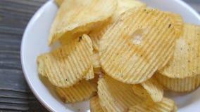 Gebratene Chips des Kartoffelchips auf Teller auf der hölzernen Tabelle, Snack-Food-Aperitif stock video
