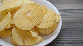 Gebratene Chips des Kartoffelchips auf Teller auf der hölzernen Tabelle, Snack-Food-Aperitif mit köstlichem und geschmackvollem a stock footage