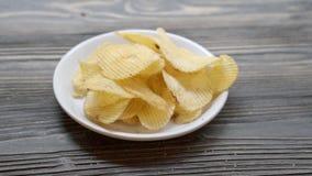 Gebratene Chips des Kartoffelchips auf Teller auf der hölzernen Tabelle, Snack-Food-Aperitif mit köstlichem und geschmackvollem a stock video footage