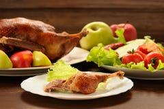 Gebratene Ente diente mit Frischgemüse und Äpfeln auf hölzernem t Stockfoto