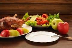 Gebratene Ente mit Frischgemüse und Äpfel und leere Platte an Stockbilder
