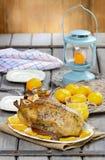 Gebratene Ente mit Orangen auf Holztisch Stockfoto