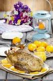 Gebratene Ente mit Orangen auf Holztisch Stockbilder