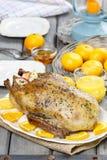Gebratene Ente mit Orangen auf Holztisch Stockbild
