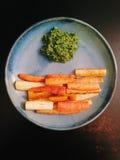Gebratene Erbstückkarotten mit Karottenspitze Pesto Lizenzfreies Stockfoto