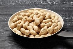 Gebratene Erdnüsse auf einem schwarzen hölzernen Hintergrund stockbild