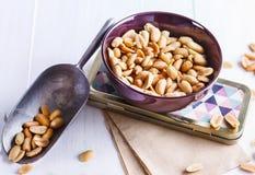 Gebratene Erdnüsse auf einer Schüssel über weißem hölzernem Hintergrund Stockbilder