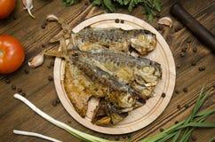 Gebratene Fische auf einem hölzernen Brett mit Gewürzen Stockfotos