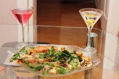Gebratene Fische auf einer Platte und zwei Gläsern mit alkoholischen Getränken Stockbild