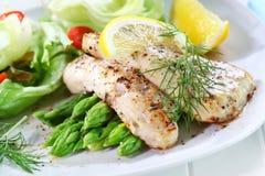 Gebratene Fische auf grünem Spargel mit Salat Lizenzfreies Stockbild