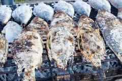 Gebratene Fische besprühen mit Salz Lizenzfreie Stockfotos