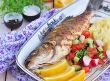 Gebratene Fische dienten mit Kartoffelpüree, Zitronenscheibe und Gemüsesalat Stockfotos