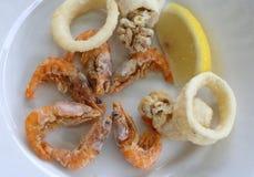 Gebratene Fische mit Garnele und einer Zitronenscheibe stockbild