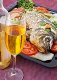 Gebratene Fische mit Gemüse. Und weißer Wein Stockbilder