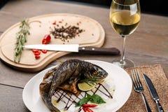 Gebratene Fische mit Glas Wein Stockbilder