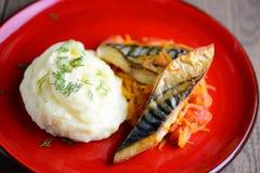 Gebratene Fische mit Kartoffelpürees auf einer roten Ronde Selbst gemachtes Lebensmittel auf einem Holztisch, brauner Hintergrund Stockfotos