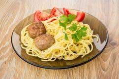 Gebratene Fleischklöschen mit Teigwaren, Petersilie und Tomaten in der Platte Stockfoto