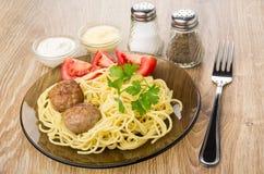 Gebratene Fleischklöschen mit Teigwaren und Tomaten in der Platte, Gewürze, Soßen Stockfotografie