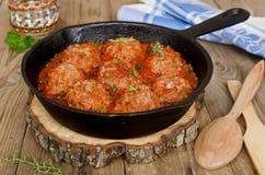 Gebratene Fleischklöschen mit Tomatensauce und Gewürzen in der Bratpfanne Stockfotografie