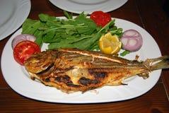 Gebratene ganze Fische mit Salat Lizenzfreie Stockfotos