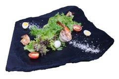 Gebratene Garnele mit Kopfsalat auf einem schwarzen Stein Stockbild