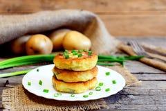 Gebratene Gemüsekoteletts Kartoffelkoteletts mit Gemüse und Gewürzen auf Platte Rohe Kartoffeln, frische Frühlingszwiebeln, Gabel Stockbild