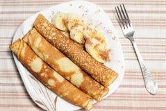 Gebratene gerollte Pfannkuchen auf einer Platte mit Scheiben der Banane und des choco Lizenzfreies Stockfoto