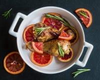Gebratene Hühnerbeine auf Scheiben von roten Orangen in der weißen Backform Schwärzen Sie Schieferhintergrund stockbild