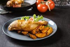 Gebratene Hühnerbeine mit Kartoffelkeilen und -tomaten Lizenzfreies Stockbild