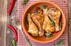 Gebratene Hühnerbeine mit Pfeffer des Rosmarins, des Knoblauchs und des roten Paprikas Lizenzfreies Stockbild