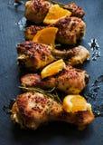 Gebratene Hühnerbeine, Orangen und Rosmarin auf dem schwarzen Hintergrund lizenzfreie stockfotos
