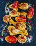 Gebratene Hühnerbeine, rote Orangen, Moosbeeren, Knoblauch und Rosmarin auf dem schwarzen Hintergrund Lizenzfreies Stockfoto