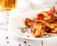 Gebratene Hühnerbeine und ein Glas Bier Stockfoto