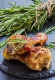 Gebratene Hühnerbeine und Rosmarin auf dem schwarzen Hintergrund lizenzfreies stockbild
