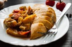 Gebratene Hühnerbrust mit Karotten, Zwiebeln und Kartoffeln diente auf einer weißen Platte Lizenzfreie Stockfotos